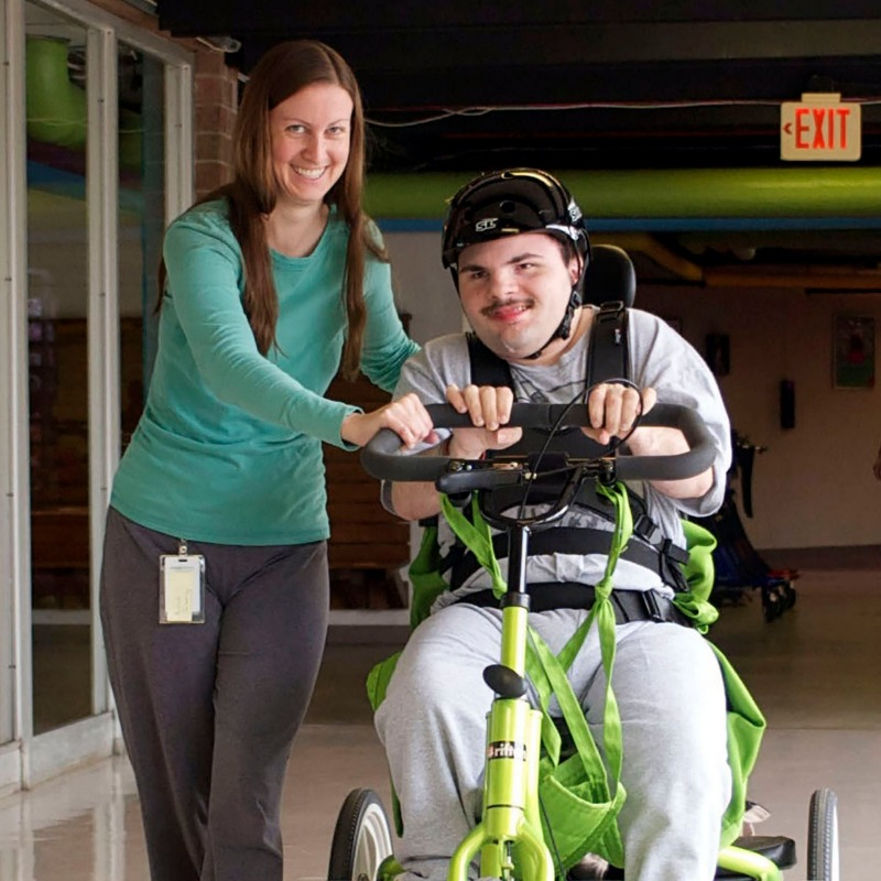 Image of a Direct Support Professional pushing one of the people we serve in a wheelchair
